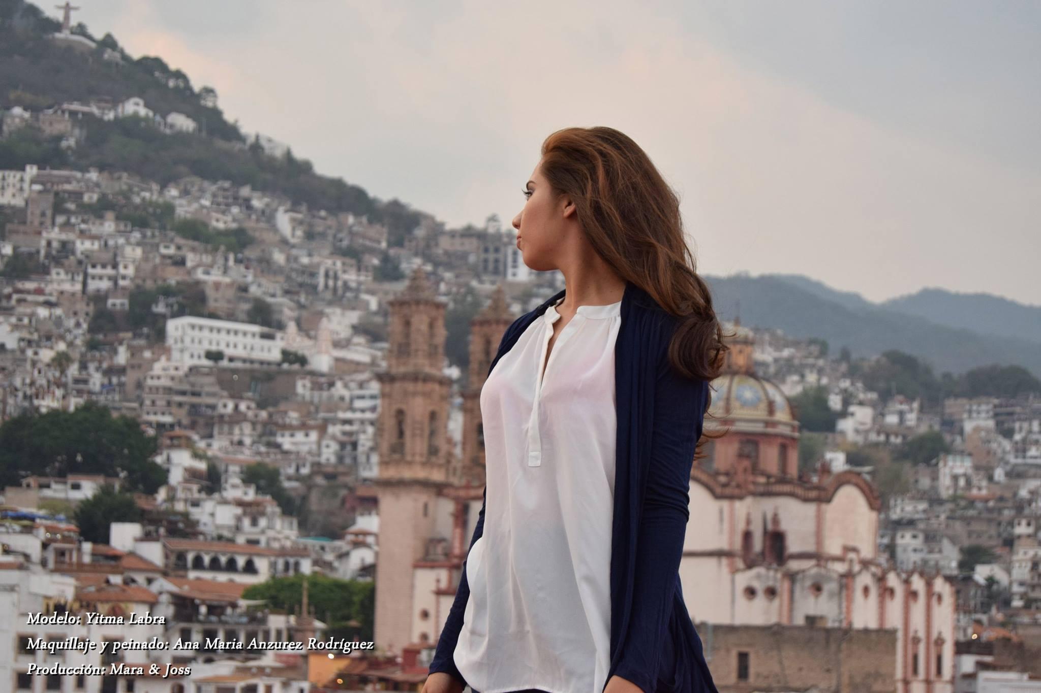 Mujer volteando atrás con blusa blanca y Taxco en el fondo