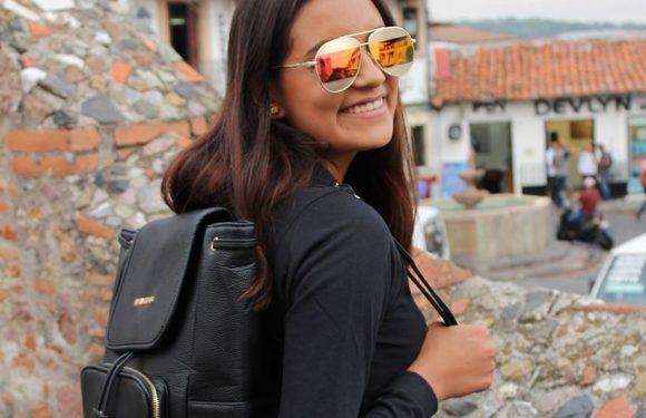 Mujer con lentes de aviador y mochila en la espalda sentada de espalda y volteando atrás
