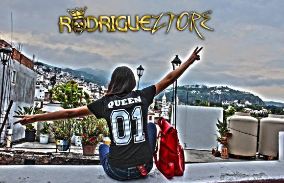 Mujer de espalda con camiseta deportiva y Taxco en el fondo. Junto a la mujer hay una mochila roja