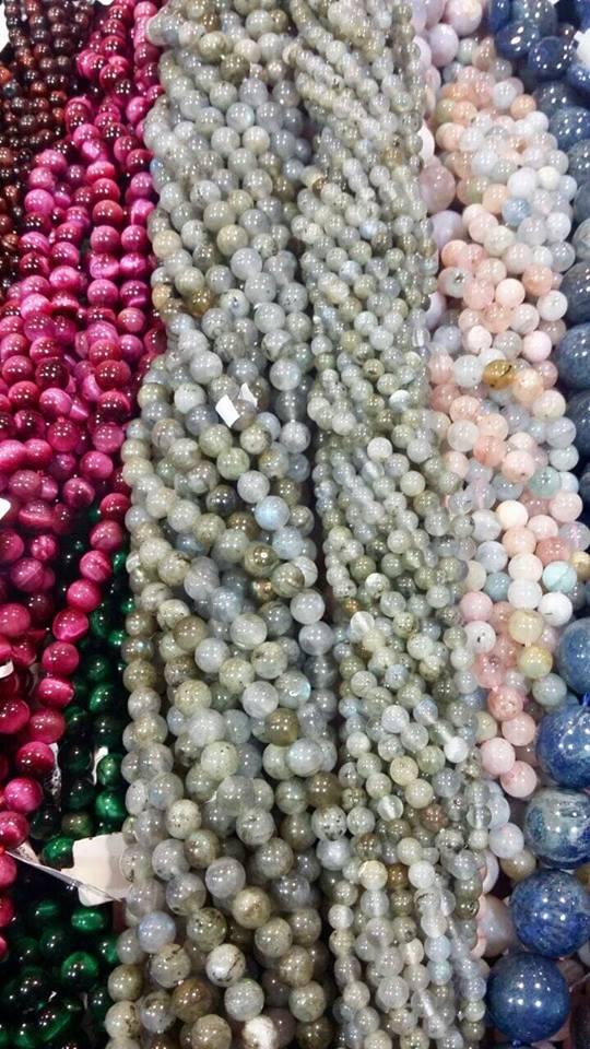 Numerosas piedras naturales cortadas en forma de pequeñas esferas de diversos colores acomodadas en distintos hilos