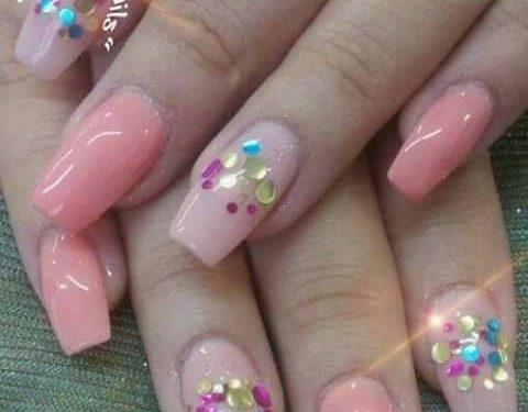Manos con uñas decoradas con brillantes
