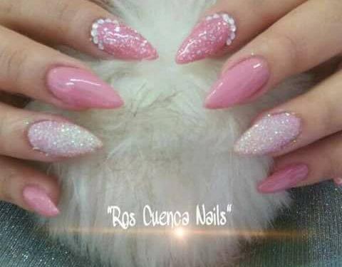 Manos con uñas pintadas y decoradas con polvo brillante