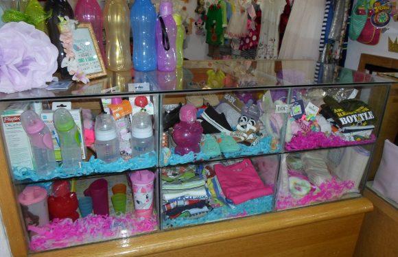 Mostrador con biberones, playeras, vasos para bebé y otros artículos para bebé