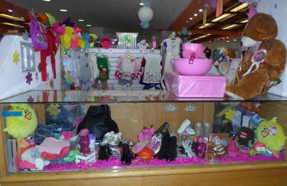 Local completo. Un mostrador al frente con accesorios para bebé y al fondo ropa para bebé